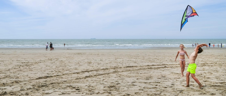 Kinderen vliegeren op strand