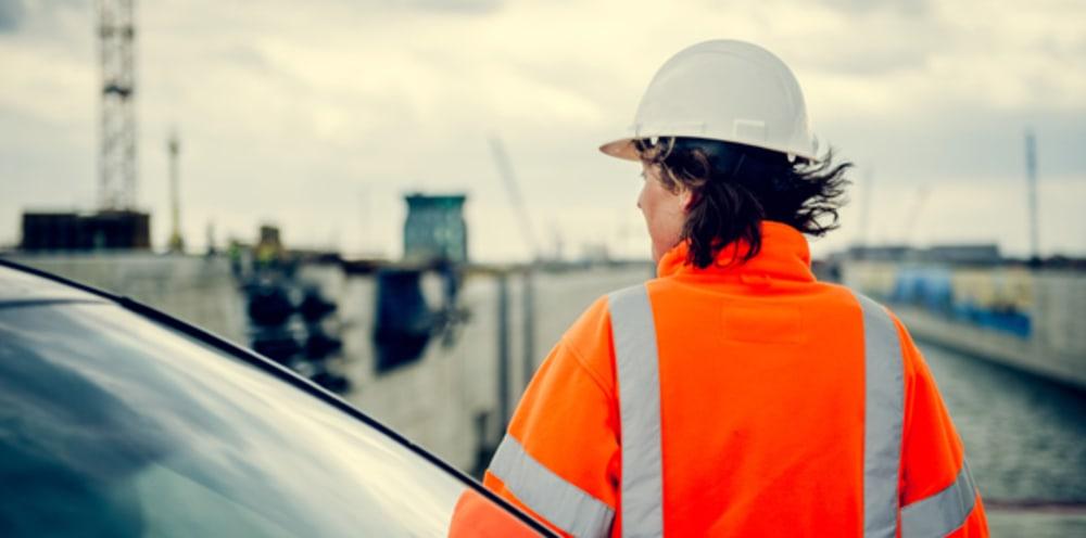 Vrouwelijke ingenieur met helm en veiligheidsvest met rug naar camera in de haven.