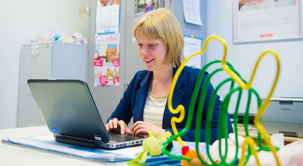 Vrouw zit achter laptop aan bureau met kinderspeelgoed