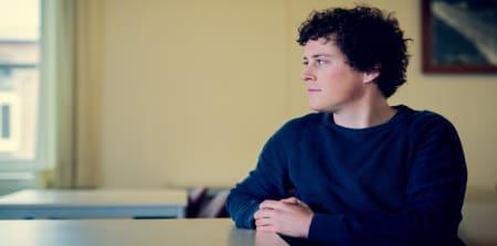 Portret van jonge man aan tafel.
