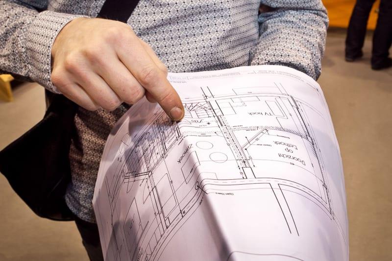Persoon wijst naar een deel van het huis op bouwplannen