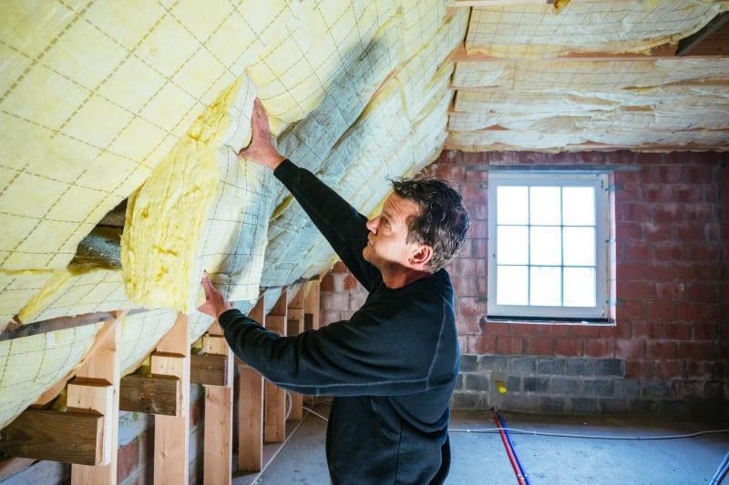 Man plaatst isolatie in dak