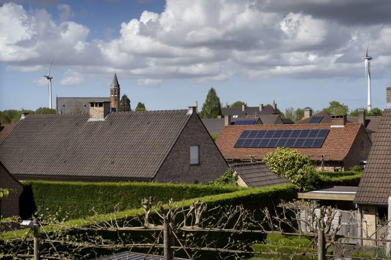 Zicht op verschillende daken en één daarvan heeft zonnepanelen