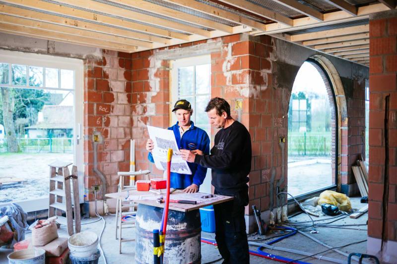 Mannen bespreken bouwplan.