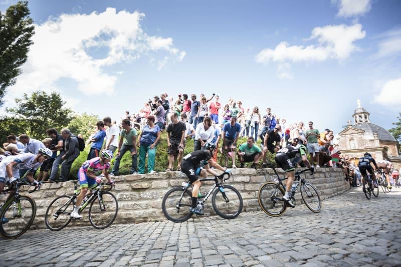 Onder aanmoediging van supporters beklimmen wielrenners een kasseistrook tijdens de Ronde van Vlaanderen.