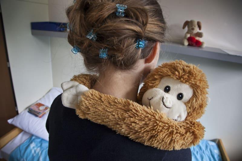 Meisje knuffelt een pop in de vorm een aapje.
