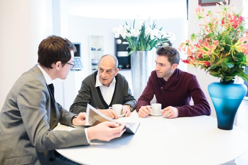 Oudere man in overleg met jonger familielid en adviseur.