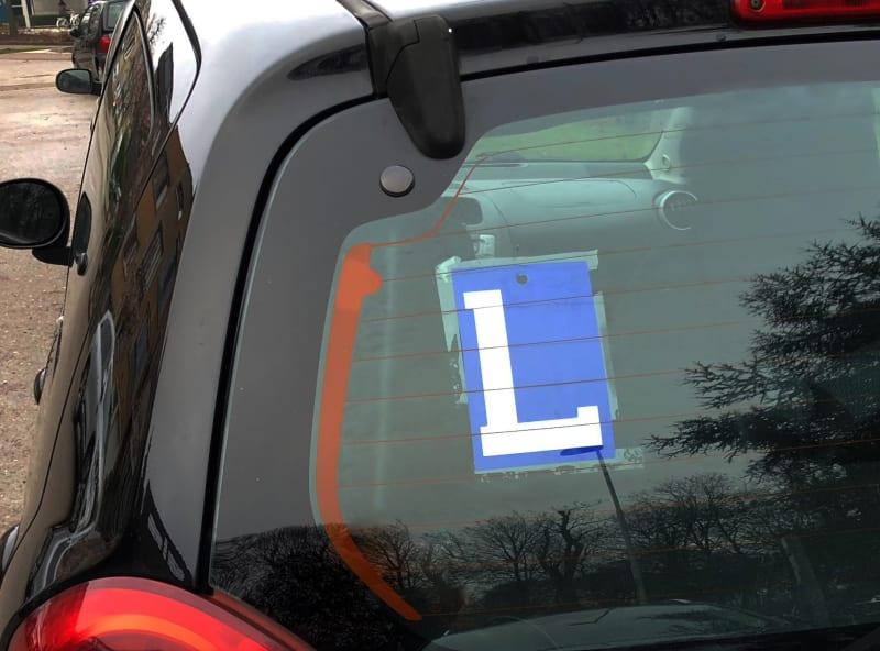 Een letter L achteraan op een auto