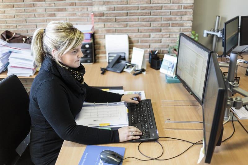 Boekhoudster werkt aan een dossier aan haar bureau.