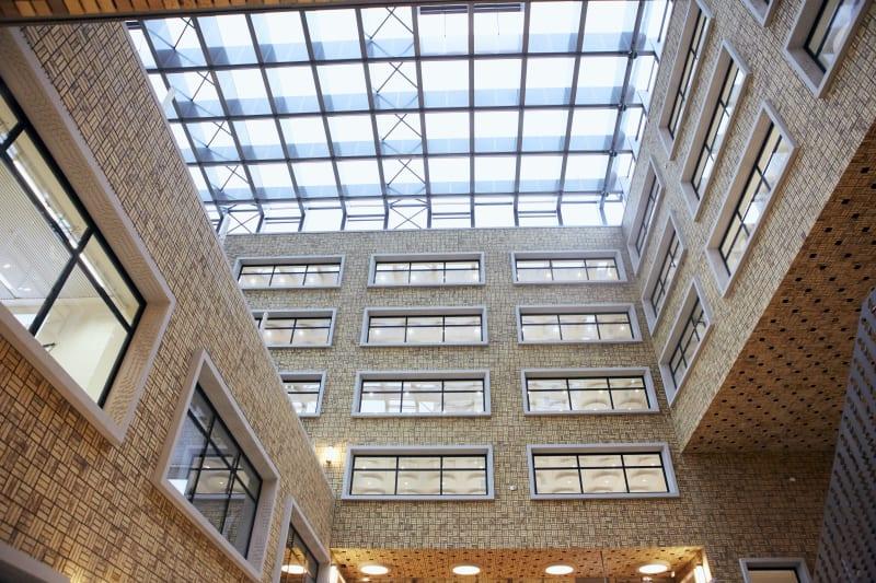 Binnenkant van kantoorgebouw met glazen plafond en ramen van verschillende verdiepingen