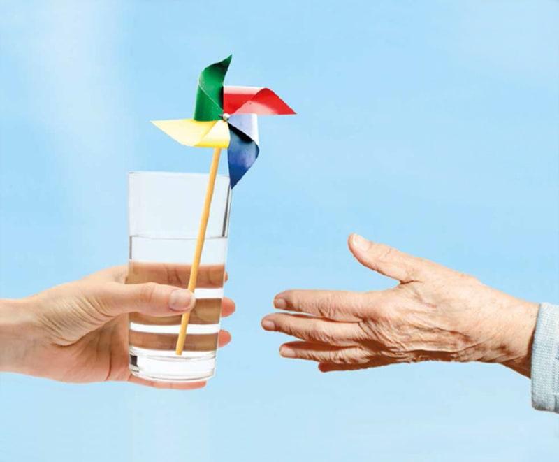 Iemand geeft glas water met windmolentje aan uitgestrekte hand