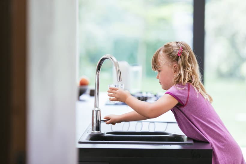 Meisje neemt water van de kraan.