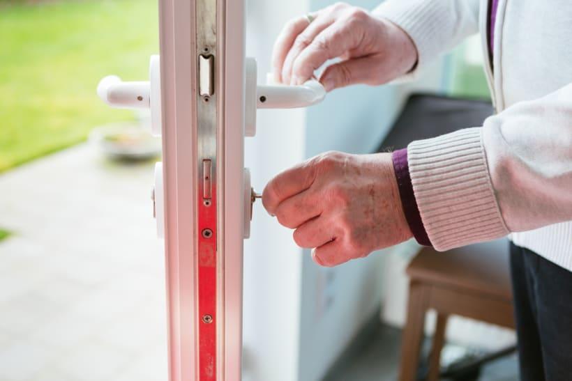 Man draait aan het slot van een deur.