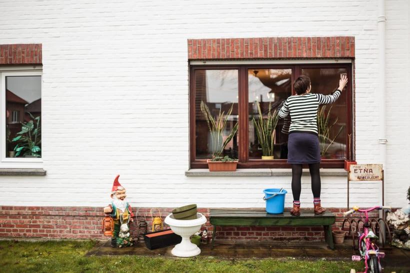 Vrouw poetst de ramen van een woning.