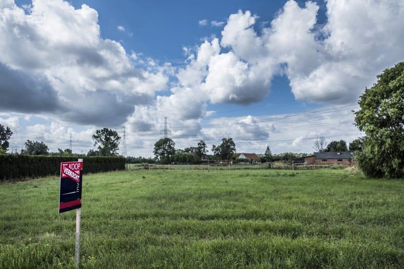 Een bouwgrond met een bordje 'verkocht'.