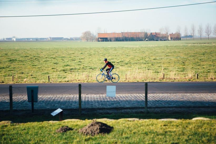 Fietser fietst tussen de polders.