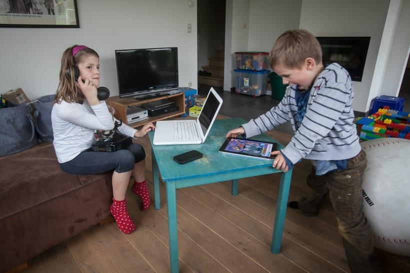 Kinderen spelen met oude telefoon en tablet.