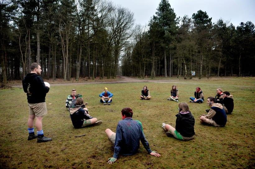 Jongeren van de jeugdbeweging zitten in een cirkel terwijl de leiding een activiteit uitlegt.