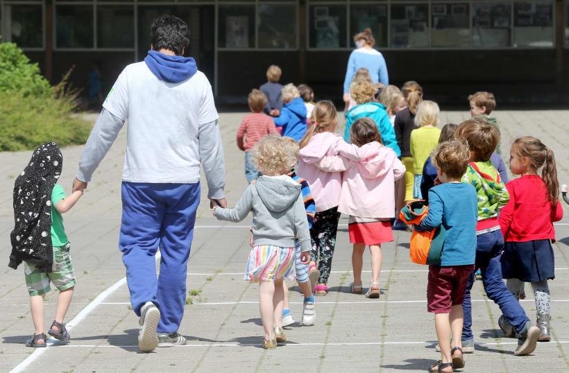 Kinderen op de speelplaats met hun begeleider.
