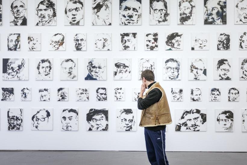 Man bekijkt muur vol kunstwerken.