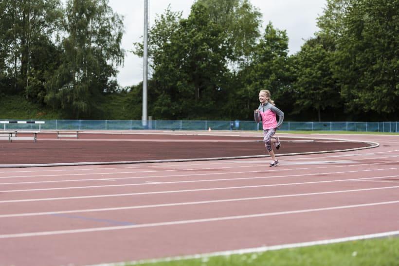 Meisje loopt op atletiekpiste.