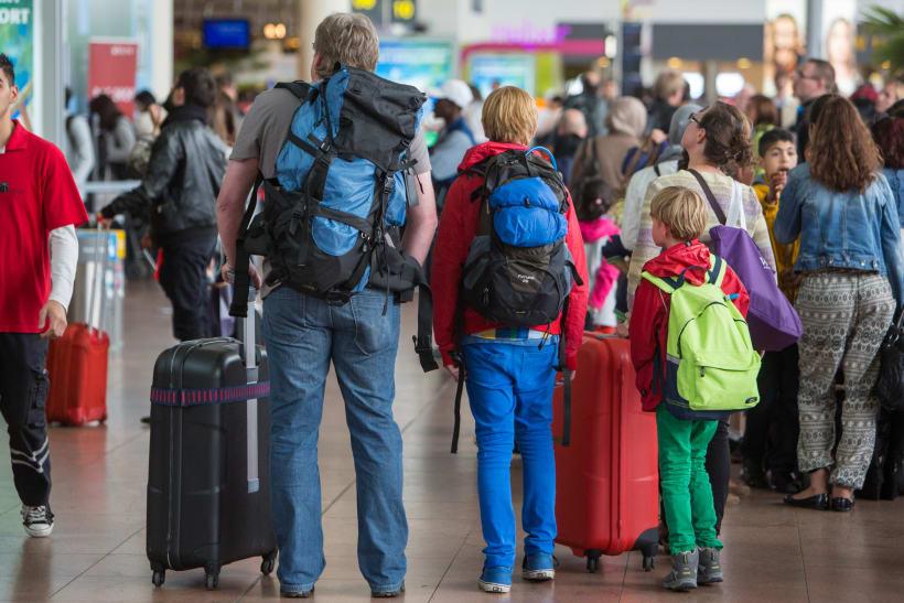 Gezin staat in luchthaven met rugzakken en reiskoffers