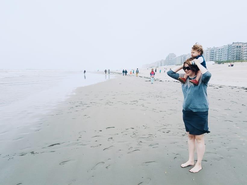 Moeder met kind op haar schouders aan de branding van de zee op het strand.