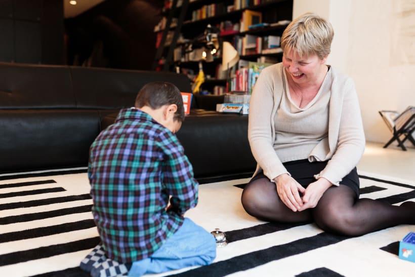 Pleegmoeder lacht naar pleegzoon tijdens het spelen van een gezelschapsspel.