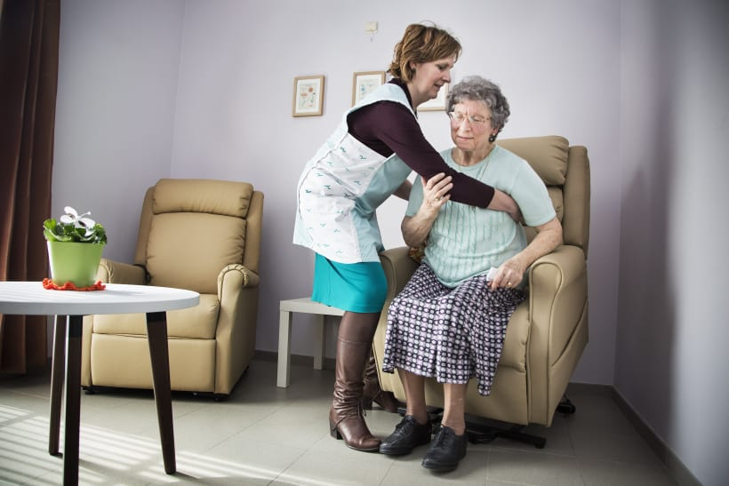 Vrouw helpt oudere vrouw in haar huiskamer