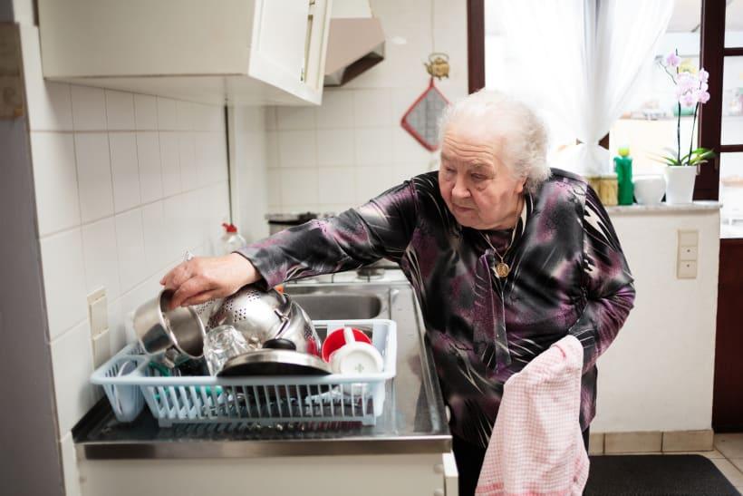 Oudere vrouw droogt de afwas af.
