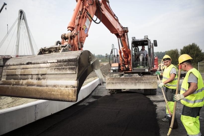 Kraan en bouwvakkers spreiden asfalt uit.