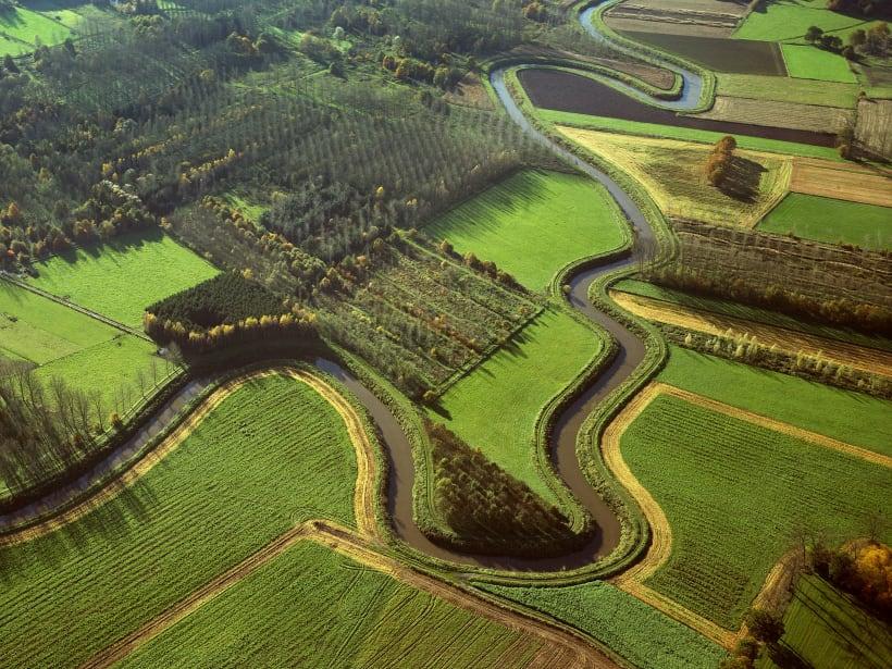 Luchtfoto van een groene omgeving met een waterloop