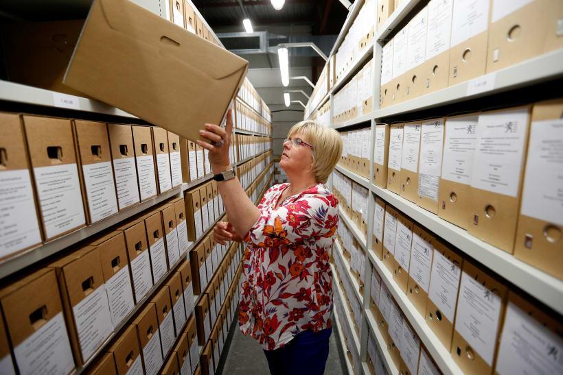 Archivaris plaatst een map in een rek.