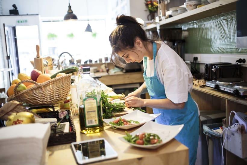 Vrouw maakt maaltijden klaar in haar eethuis.