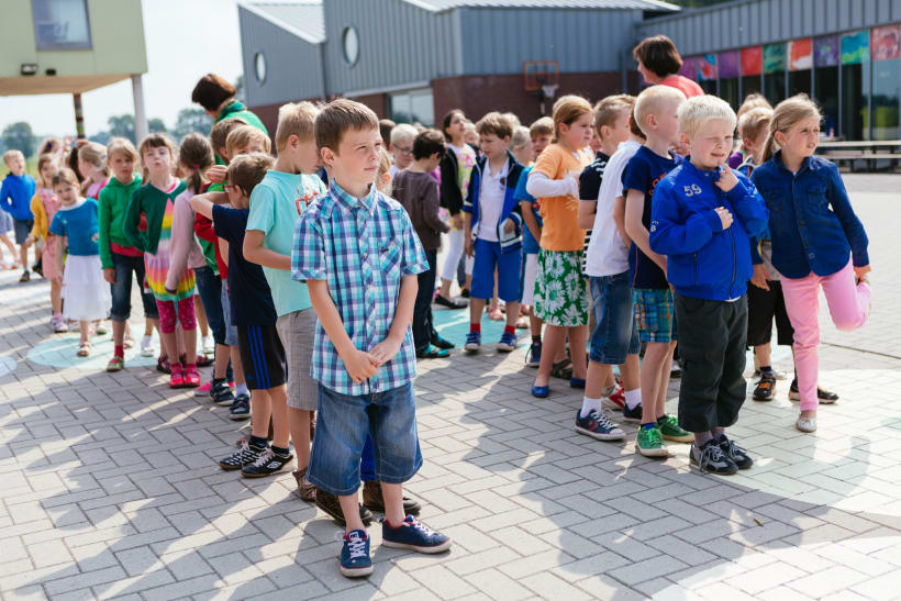 Kinderen staan in de rij op de speelplaats.
