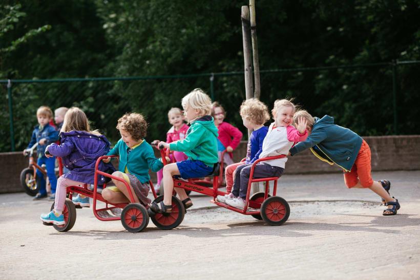Kinderen spelen met gocarts op de speelplaats.