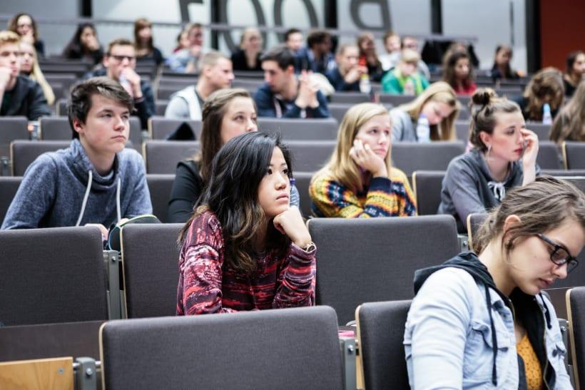 Studenten luisteren aandachtig in de aula.
