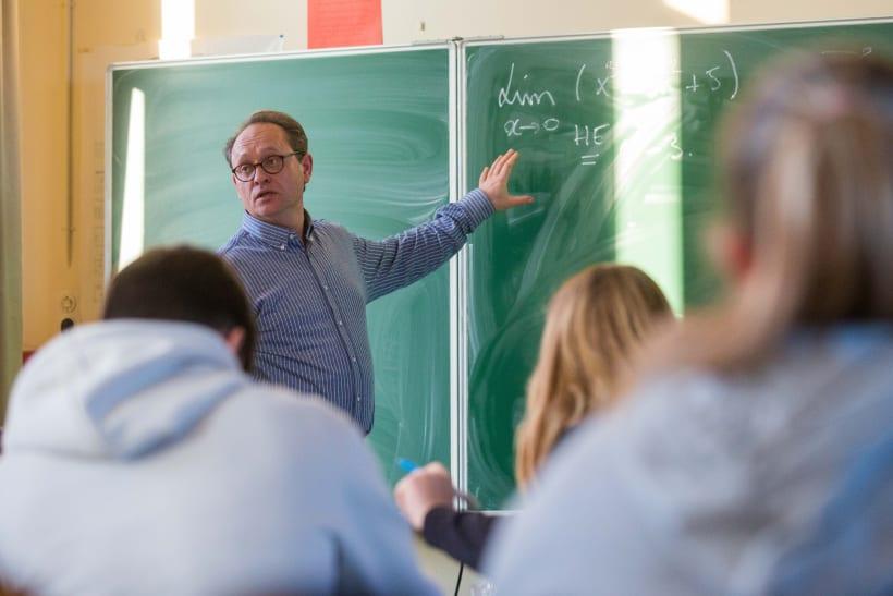 Leerkracht aan het groene bord in een klas met leerlingen