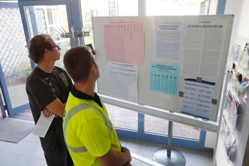Twee mannen kijken naar de lijsten in een stembureau