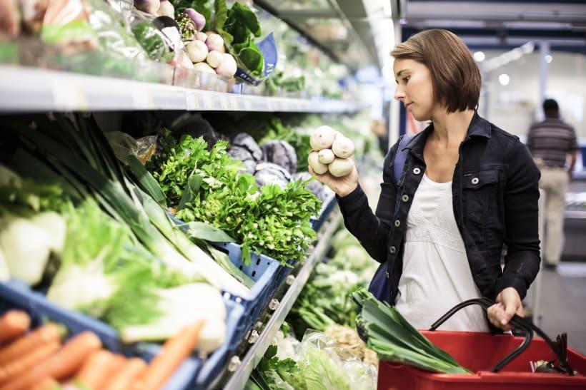Vrouw kies groenten uit in de supermarkt.