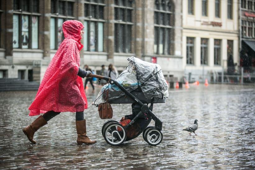 Vrouw met baby in buggy op straat