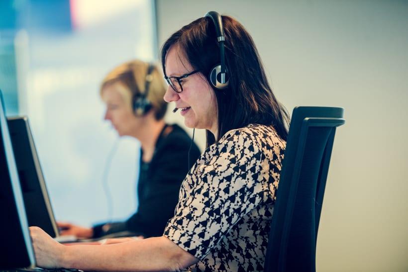 Personeelsleden met hoofdtelefoon aan de laptop