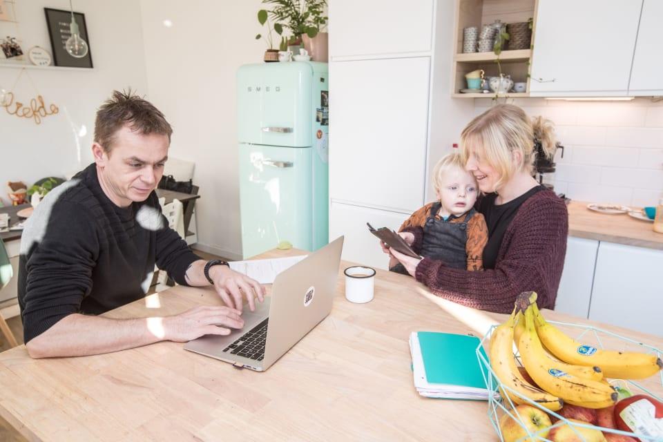 Een man zit aan tafel in de keuken of eetkamer op de laptop te werken. Zijn vrouw zit naast hem en houdt hun zoon op haar schoot vast, terwijl ze op haar gsm scrolt.
