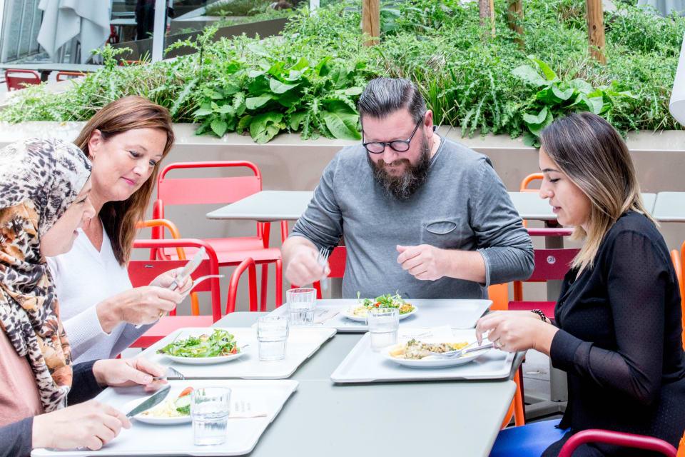 Een groep collega's eet samen aan een tafeltje in het restaurant tijdens de lunchpauze