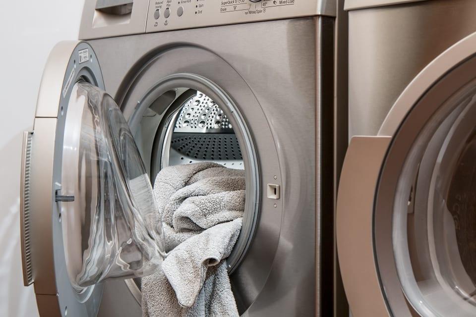 Een handdoek hangt uit de wasmachine.