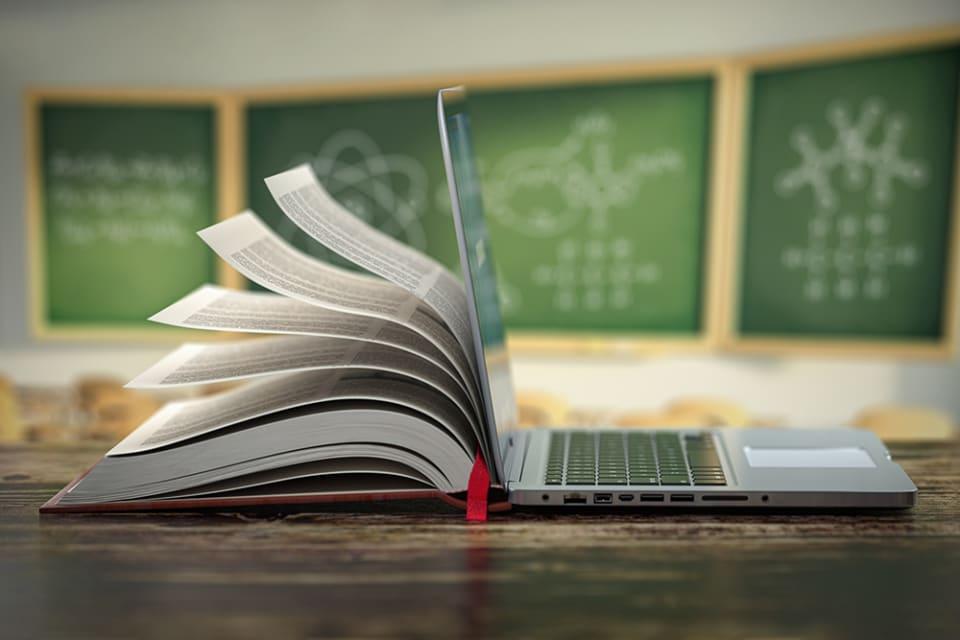 Een open boek op een lessenaar in een klaslokaal, de pagina's waaien open en gaan over in een laptop