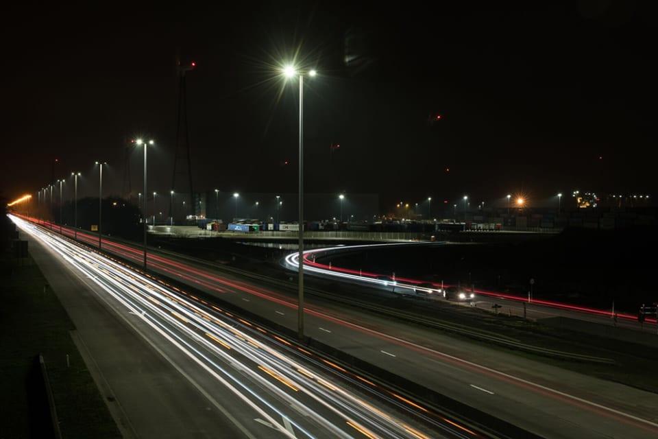 Een autosnelweg in het donker, verlicht met lantaarnpalen