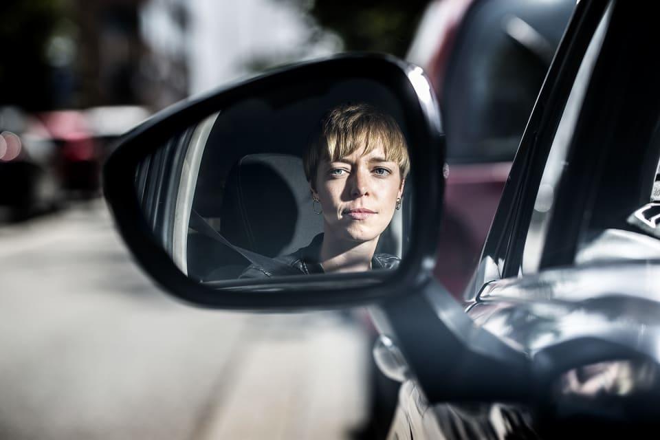 Jongere in de auto met zijspiegel