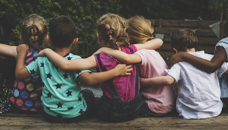 Groepje kinderen zit met de armen over elkaars schouders met de rug nar de camera