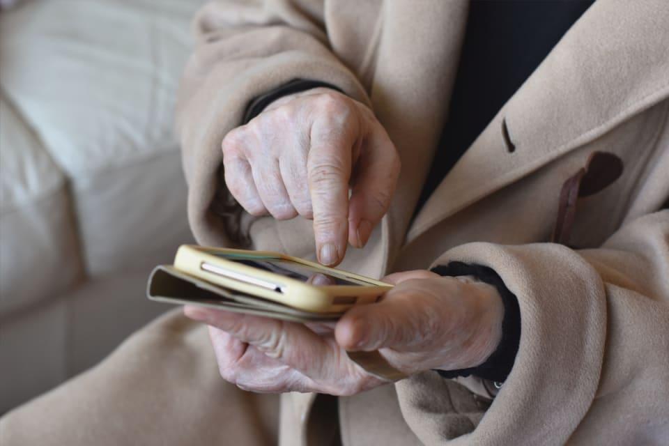 Oudere persoon met smartphone in de hand